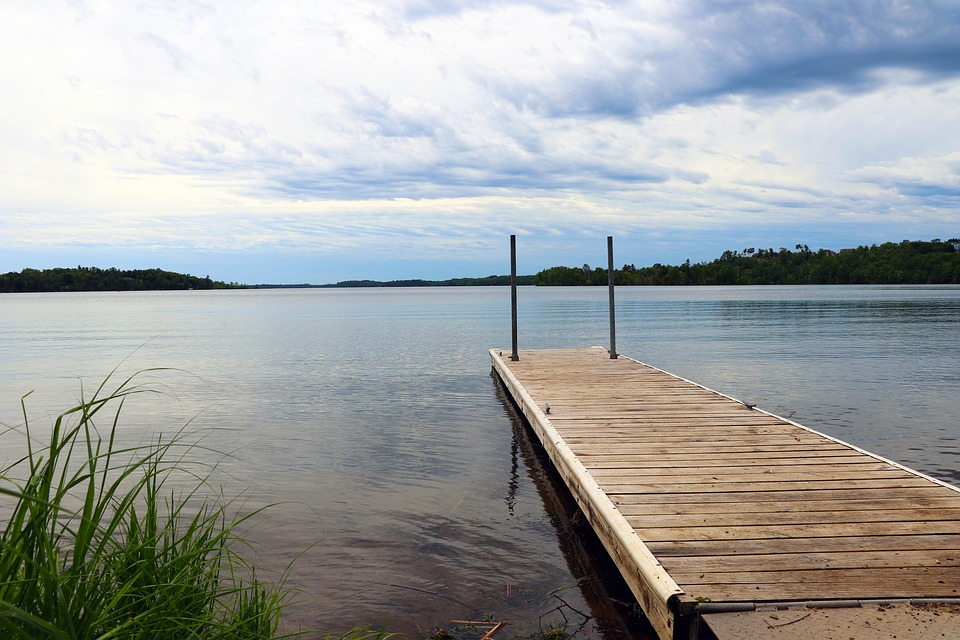 dock by lake under cloudy sky