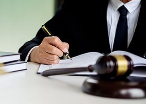 Halifax Accident lawyer writing at desk with gavel on it