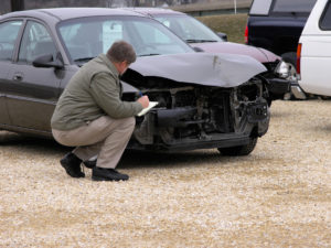 a man taking notes in front of a crashed car