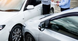 Insurance agent writing on clipboard while examining car after accident claim